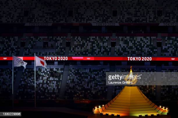 Detailed view of the Olympic cauldron lit next to the Japanese and Olympic flags during the Opening Ceremony of the Tokyo 2020 Olympic Games at...