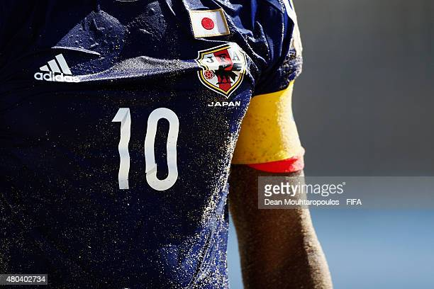 A detailed view of the shirt number 10 JFA logo captians arm band and Japan flag all covered in sand worn by Ozu Moreira during the Group A FIFA...