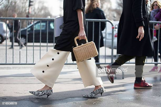 Details a showgoer carries a basket weave purse wears widelegged cream trousers with buttons and Celine zebra print low heeled shoes at the Chanel...