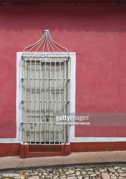 Details of a colorful window in Trinidad with traditional wrought iron caging, Cuba