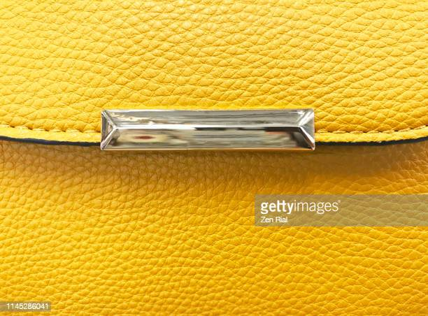 details of a vibrant yellow ladies handbag with silver colored metal decor on flap - leather purse stock pictures, royalty-free photos & images