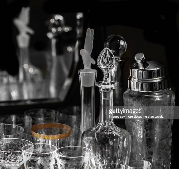 Details of bottles and wine glasses reflected in a mirror. Still life.