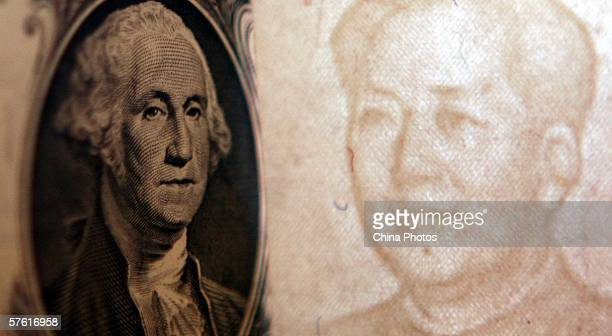 Details of dollar and a yuan notes are seen at a bank on May 15 2006 in Beijing China China's official exchange rate rose today to 79982 yuan per US...