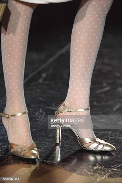 Details of stockings and gilded sandals