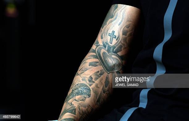 Details of the tattooed arm of Mercedes AMG Petronas British driver Lewis Hamilton is pictured as he gives an interview to television channel at the...