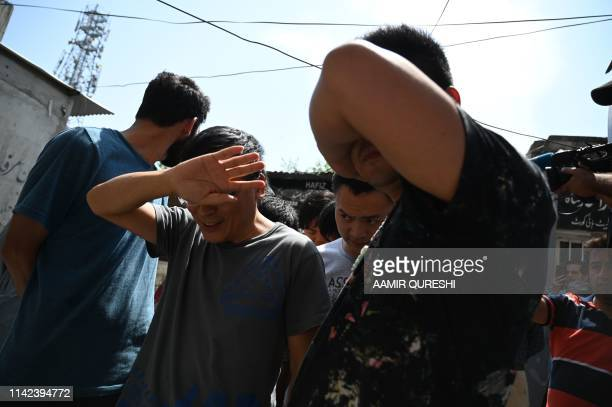 Detained and handcuffed Chinese nationals hide their faces as they arrive at a court after being arrested by the Pakistani Federal Investigation...