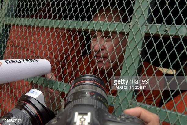 Detained Australian filmmaker James Ricketson speaks to journalists from a prison vehicle on his arrival at Phnom Penh court for his continuing trial...