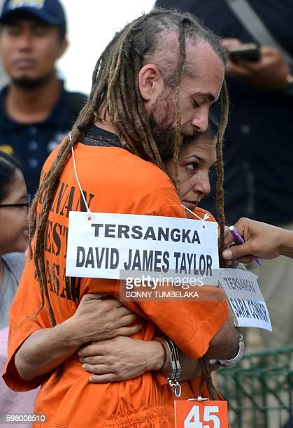 Detained British national David Taylor and Australian national Sara Connor embrace during the reenacting of events at the crime scene were an...