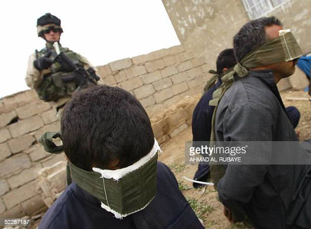 Detained Iraqis sit on the ground blindfolded during Operation Casablanca in the Dora district of southern Baghdad 07 March 2005 About 500 US...