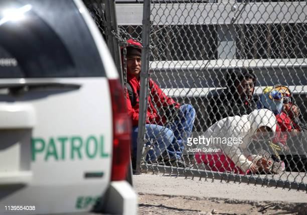 Detained migrants look on as they wait to be transported by the US Border Patrol at the border of the United States and Mexico on March 31 2019 in El...