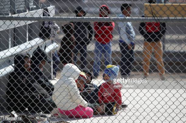 Detained migrants wait to be transported by the US Border Patrol at the border of the United States and Mexico on March 31 2019 in El Paso Texas US...