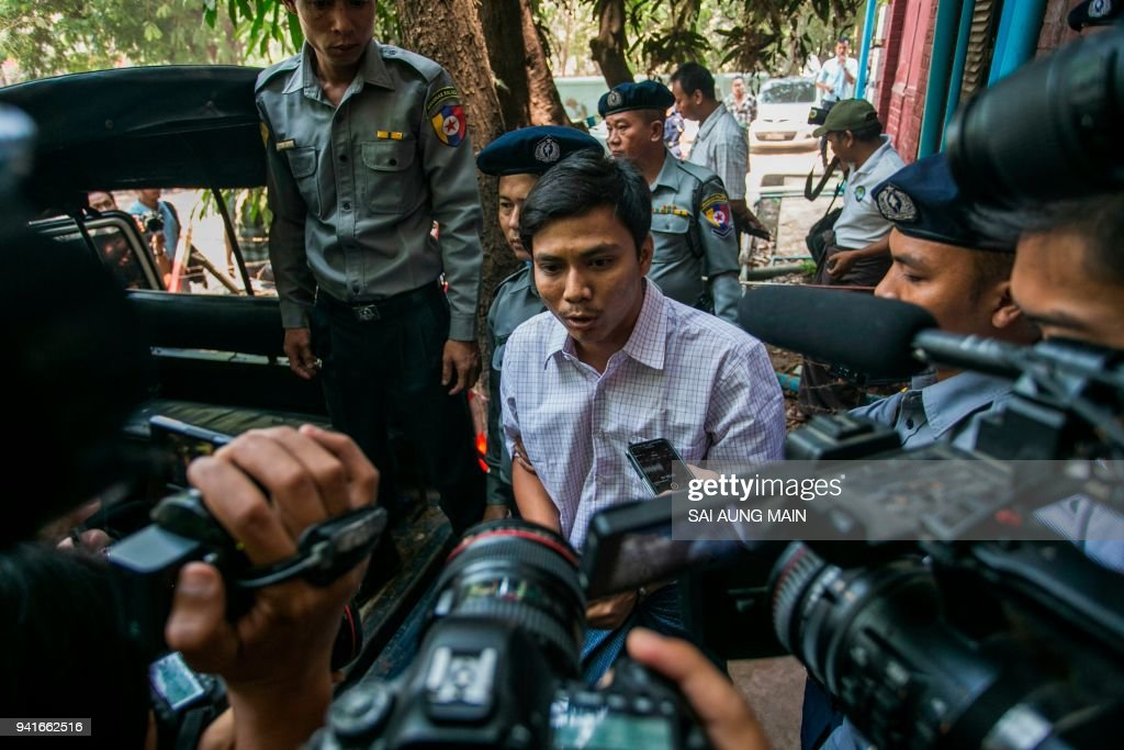 Detained Myanmar journalist Kyaw Soe Oo (C) is flanked by reporters as he is being escorted to a police van from a courthouse after attending his trial in Yangon on April 4, 2018. The two Myanmar reporters are charged under a secrecy act that could see them face up to 14 years in jail, in a case that has sparked an outcry over shrinking media freedom. /
