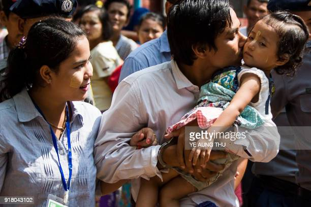 Detained Myanmar journalist Kyaw Soe Oo kisses his daughter as he is escorted by police to a court in Yangon to face trial on February 14 2018 The...