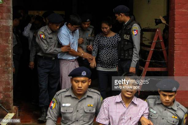 Detained Myanmar journalists Kyaw Soe Oo and Wa Lone are escorted by police from a courthouse following their ongoing pretrial hearing in Yangon on...