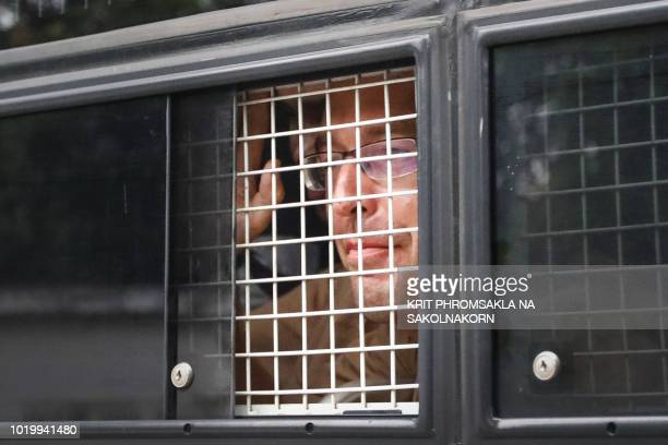 Detained Russian seduction guru Alex Kirillov leaves in a prison van after appearing before a court trial in Pattaya together with Belarusian model...