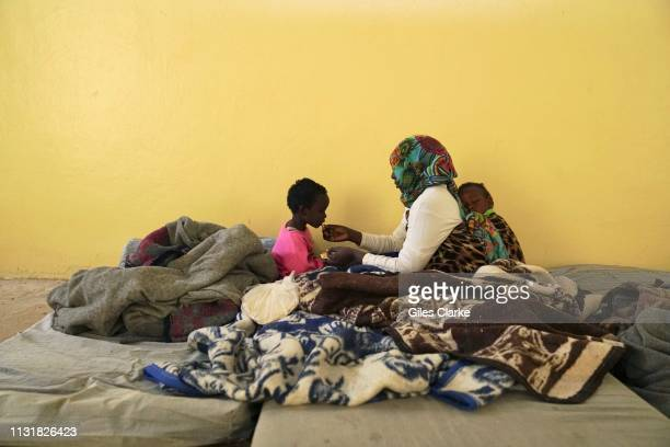 Detained Sudanese mother, with sleeping baby on her back, feeds her other child some bread inside the female room of the Qanfoodah detention center...