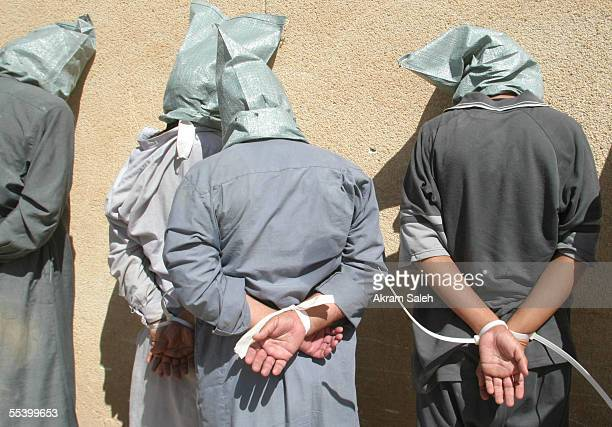 Detained suspected insurgents stand with hoods on their heads and their hands bound behind their backs in the alQadisiyah neighborhood after...