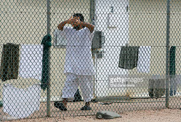 A detainee covers his face while moving inside Camp 1 at the detention facility at the US Naval Station October 2 2007 in Guantanamo Bay Cuba About...