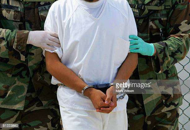 A detainee is escorted by military police at Camp 4 of the maximum security prison Camp Delta at Guantanamo Naval Base August 26 2004 in Guantanamo...