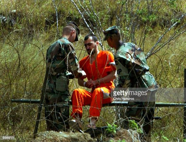 A detainee is placed on a gurney by Marines in Camp XRay February 6 2002 in Guantanamo Bay Cuba Many of the 156 AlQaeda or Taliban detainees are...