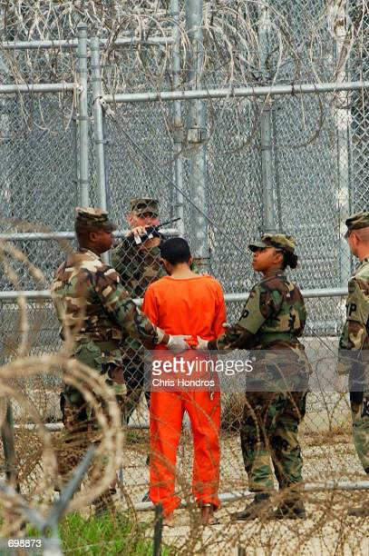 A detainee is taken from a questioning session at camp XRay February 6 2002 in Guantanamo Bay Cuba The 156 Al Qaeda and Taliban prisoners are...