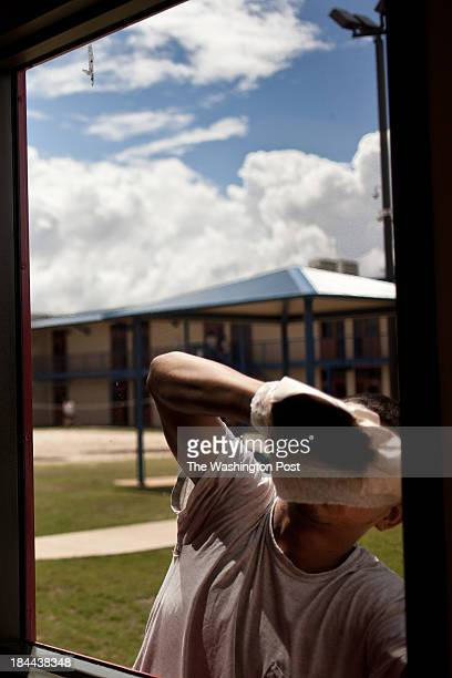 Detainee of the Karnes County Civil Detention Center cleans windows at the facility on September 9th, 2013 in Karnes County, Texas.