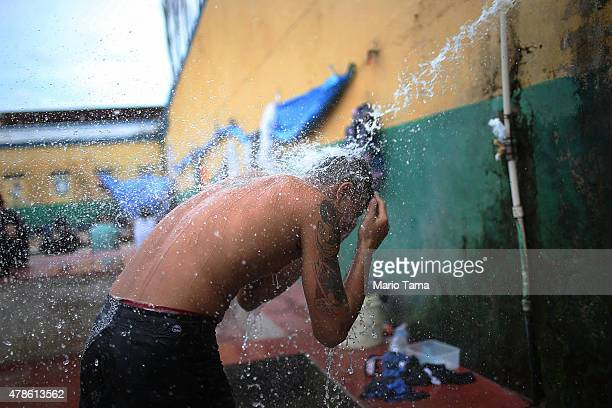 A detainee uses a makeshift shower in the recreation yard of the overcrowded Desembargador Raimundo Vidal Pessoa penitentiary inaugurated in 1904 on...