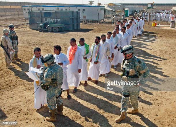 Detainees are checked by US soldiers during a prisoner release on October 1 2005 at Abu Ghraib prison 25 kms west of Baghdad About 500 Iraqi...