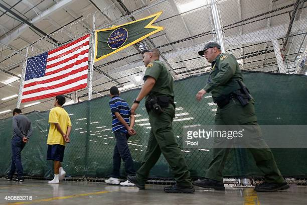 Detainees are escorted to an area to make phone calls as hundreds of mostly Central American immigrant children are being processed and held at the...