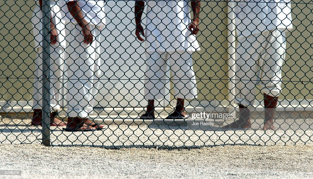 Detainees from the U.S. war in Afghanistan stand near their cell blocks at Camp Delta April 7, 2004 in Guantanamo Bay, Cuba. On April 20, the U.S. Supreme Court is expected to consider whether the detainees can ask U.S. courts to review their cases. Approximately 600 prisoners from the U.S. war in Afghanistan remain in detention.