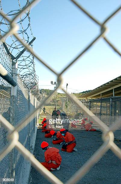 Detainees in orange jumpsuits sit in a holding area under the watchful eyes of Military Police at Camp X-Ray Januaryt 11, 2001 at Naval Base...