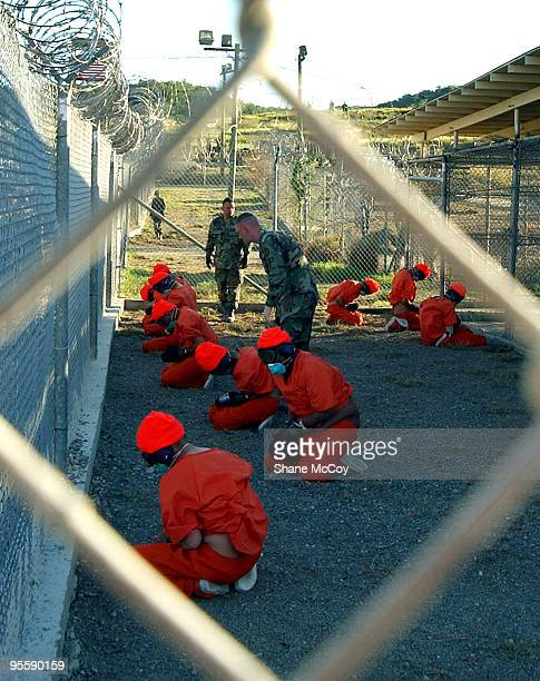 Detainees in orange jumpsuits sit in a holding area under the watchful eyes of Military Police at Camp XRay at Naval Base Guantanamo Bay Cuba during...