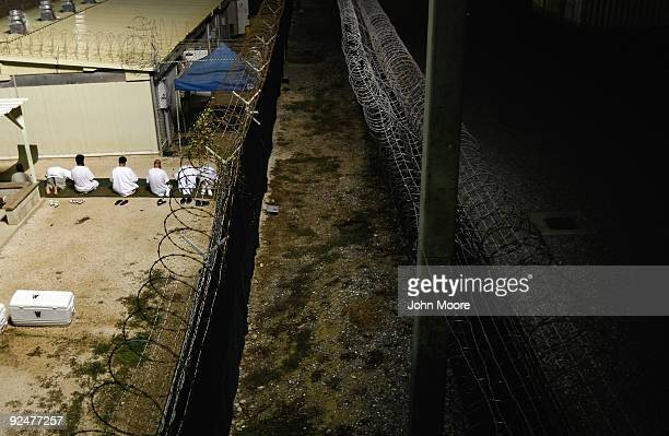 "Detainees kneel during an early morning Islamic prayer at the U.S. Military prison for ""enemy combatants"" on October 28, 2009 in Guantanamo Bay,..."