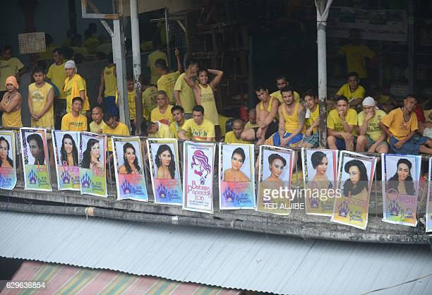Detainees relax next to photos of gay inmates for a beauty contest inside the jail complex in Quezon City suburban Manila on December 14 2016 China...