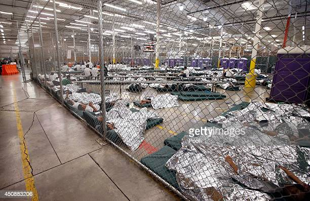 Detainees sleep and watch television in a holding cell where hundreds of mostly Central American immigrant children are being processed and held at...