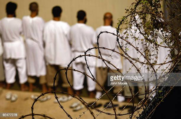 "Detainees stand during an early morning Islamic prayer at the U.S. Military prison for ""enemy combatants"" on October 28, 2009 in Guantanamo Bay,..."
