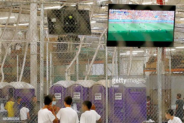 Detainees watch a World Cup soccer match from a holding cell where hundreds of mostly Central American immigrant children are being processed and...