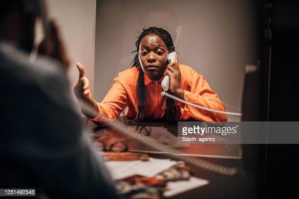 detective and female prisoner sitting in visiting room - confession law stock pictures, royalty-free photos & images