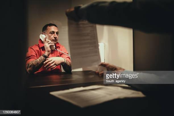 訪問室に座っている刑事と囚人 - fbi ストックフォトと画像
