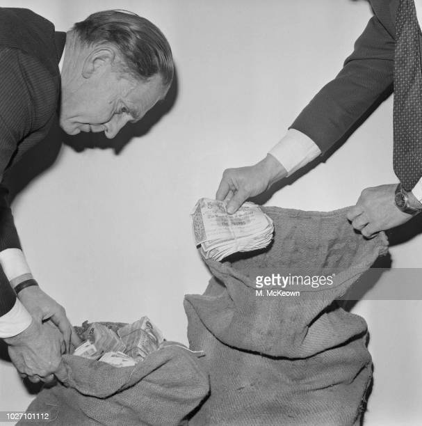 Detective Chief Inspector Syd Bradbury of the Metropolitan Police checks mailbags full of £50000 pounds in five pound and one pound notes recovered...