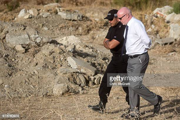 Detective Inspector Jon Cousins of the South Yorkshire Police talks with a team member as they walk past rubble at the new second search site...