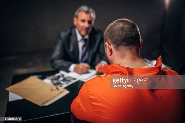 detective interrogating a male prisoner in interrogation room - prisoner photos stock pictures, royalty-free photos & images