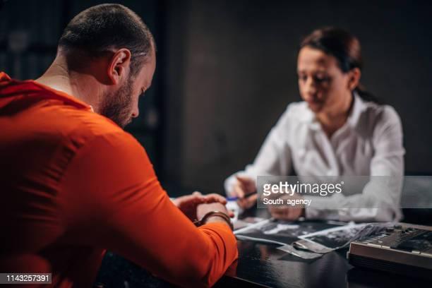 detective interrogating a man prisoner in interrogation room - prisoner stock pictures, royalty-free photos & images