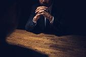 Detective interviewing suspect in dark private room