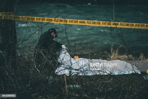 detective investigating crime scene by the river - criminal investigation stock pictures, royalty-free photos & images