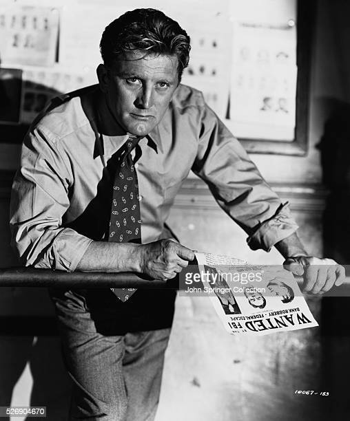 Detective James McLeod holds an FBI Wanted sheet in a scene from the 1951 film Detective Story