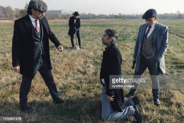 detective kneeling and looking at gang leader. - dead gangster stock pictures, royalty-free photos & images