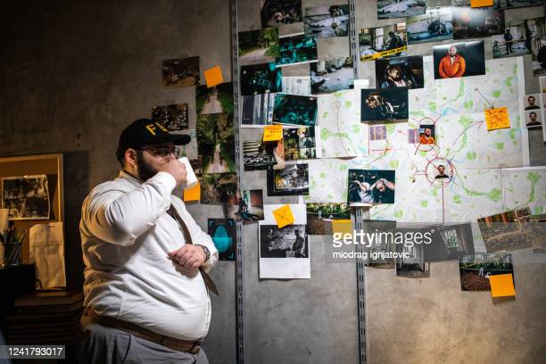 fbi detective looking at city map with photographs on wall and trying to solve the case - privateinvestigator stock pictures, royalty-free photos & images