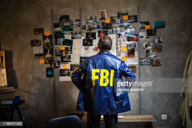 fbi detective looking at wall full of evidences and crime scene pictures - fbi stock pictures, royalty-free photos & images