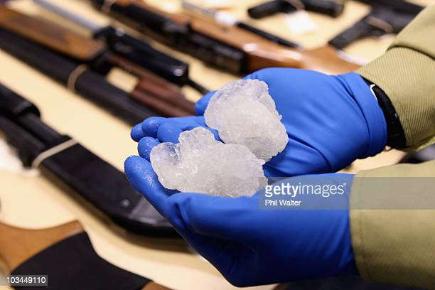 Detective Paul Baker holds two rocks of crystal meth with a street value of NZD$83000 alongside firearms that were confiscated as part of Operation...